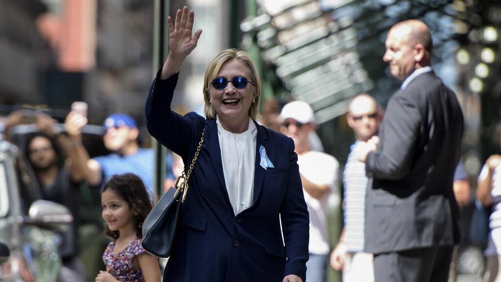 Hillary Clinton, dimanche 11 septembre 2016, salue les journalistes en sortant de l'appartement de sa fille Chelsea, où elle s'est reposée après son malaise lors des commémorations du 11-Septembre.
