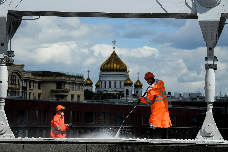 Dos trabajadores limpian el puente Krymsky sobre el río Moskva, con la Catedral de Cristo Salvador vista de fondo en el centro de Moscú, el 20 de mayo de 2020.