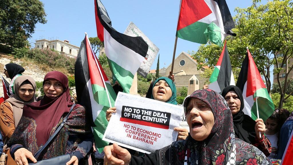 Un manifestante ondea una bandera palestina frente a las fuerzas israelíes el 25 de junio de 2019 durante una protesta contra el taller de Bahréin, cerca del asentamiento judío de Beit El, en Cisjordania.
