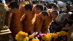 Des moines bouddhistes présentent des offrandes au dieu hindou Brahma, lors de la réouverture du sanctuaire de Bangkok, le 19 août 2015.