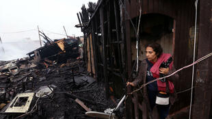 Una mujer se encuentra en medio de los escombros después del incendio en el barrio de San Juan Bosco en la ciudad portuaria de Callao, cerca de Lima, Perú, el 25 de julio de 2019.