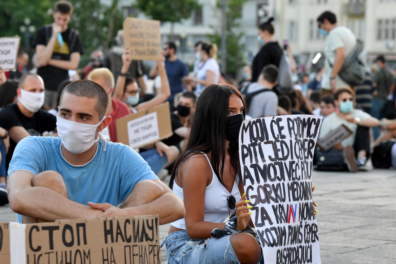 """Des manifestants assis dans la rue devant le Parlement, brandissant des pancartes indiquant """"Ne battez pas votre propre peuple"""", lors d'une manifestation à Belgrade le 9 juillet 2020."""