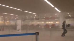 Une personne tente de fuir le hall de l'aéroport de Zaventem au milieu d'un épais écran de fumée, le 22 mars 2016.