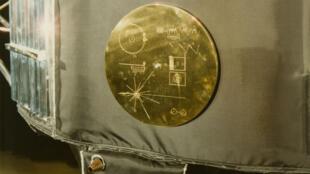 Une plaque dorée avec plusieurs symboles représentatifs de l'humanité, attachée à la sonde Voyager 2.