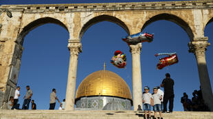 Dos niños juegan con globos junto a la Explanada de las Mezquitas en Jerusalén mientras los musulmanes y judíos conmemoran en la zona sus respectivas fechas sagradas el 11 de agosto de 2019.
