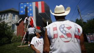 """L'artiste new yorkais Scott LoBaido (à gauche sur l'échelle) installe un T """"patriotique et végétal"""" en soutien à Donald Trump, le 9 août 2016, à Staten Island."""