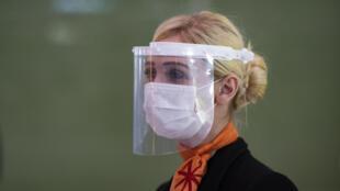 Una empleada del aeropuerto francés Charles de Gaulle con mascarilla y visera protectoras trabaja en la Terminal 2 del aeródromo internacional, el 14 de mayo de 2020 a las afueras de París