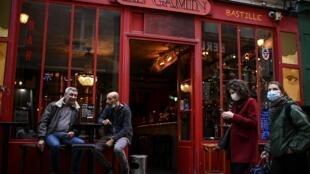 Dos mujeres con masacarilla pasan frente a un bar de París a cuya puerta dos clientes se toman algo, el 3 de octubre de 2020 en la capital francesa