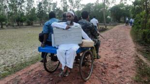 Des fonctionnaires indiens transportent une machine à vote électronique pour se rendre au bureau de vote de l'île de Ghoramara, à environ 110km au sud de Calcutta, le 18 mai 2019.