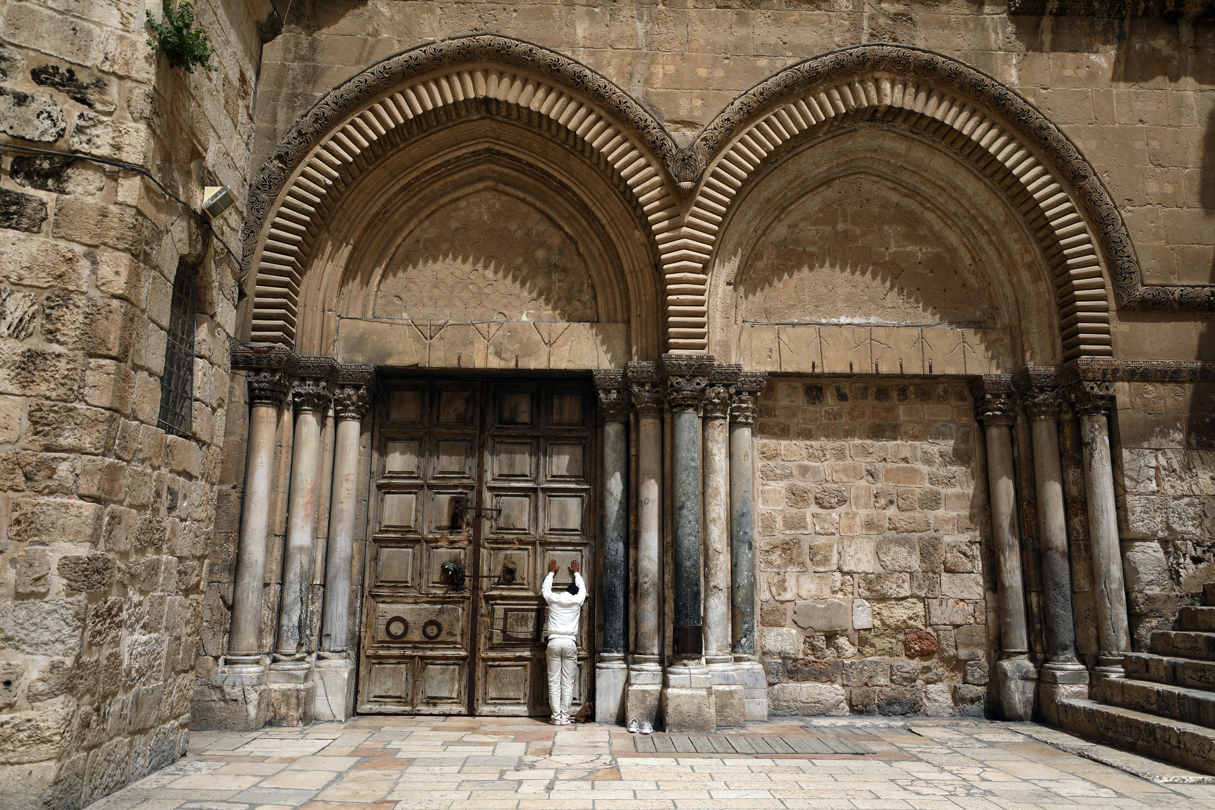 A man prays before closed doors of the Church of the Holy Sepulchre in Jerusalem's Old City on April 5, 2020.