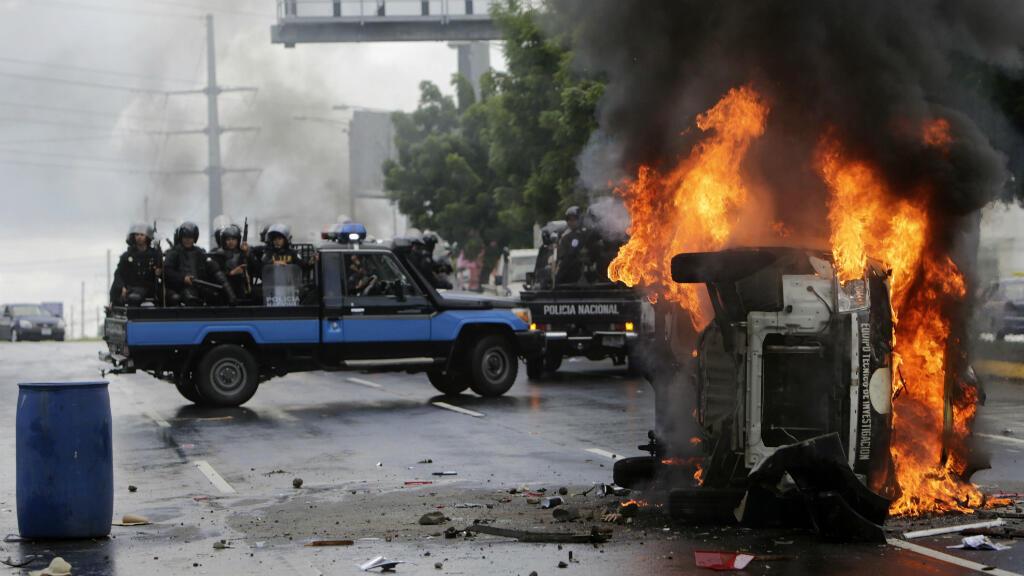 Los oficiales de la Policía Nacional con equipo antidisturbios conducen junto a un vehículo policial incendiado, volcado, después de una protesta antigubernamental en Managua, Nicaragua, el 2 de septiembre de 2018.