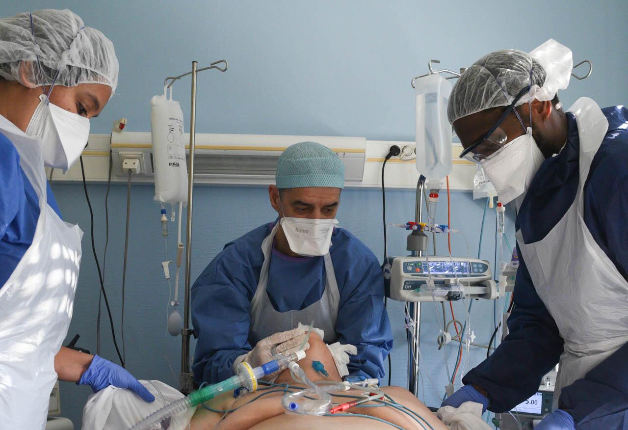 Olivier Lanza (au centre), infirmier, soutient la tête d'un patient intubé. Les patients Covid-19 sont régulièrement retournés sur le ventre, car cela augmente naturellement la ventilation du poumon. La manipulation des patients intubés est toujours un moment délicat.