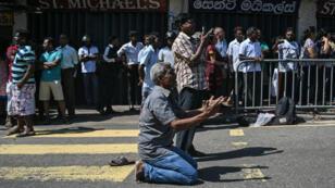 Des gens prient dans la rue au lendemain des attaques perpétrées au Sri Lanka.