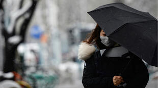 A woman wearing a face mask holds an umbrella amid snowfall on a street, following an outbreak of the novel coronavirus in the country, at Sanlitun shopping area on Valentine's Day in Beijing, China February 14, 2020.