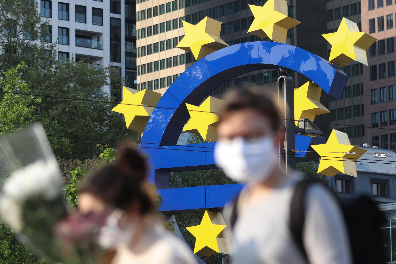 Ciudadanos con mascarillas cruzan un gran símbolo del Euro en Frankfurt, Alemania, el 24 de abril de 2020.