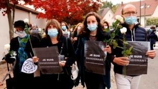 Maestros depositan flores frente a la escuela secundaria Bois d'Aulne para presentar sus respetos por el asesinato de un colega en Conflans-Sainte-Honorine, en las afueras de París, Francia, el 17 de octubre de 2020.