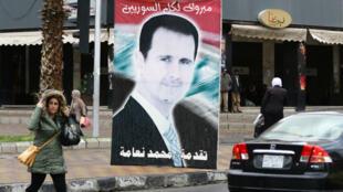 Une passante syrienne, à Damas, devant un poster du leader syrien, le 15 mars 2016.