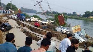 Las personas se reúnen cerca de una carretera dañada después de un terremoto de magnitud 5,8 en Mirpur, Pakistán, 24 de septiembre de 2019.