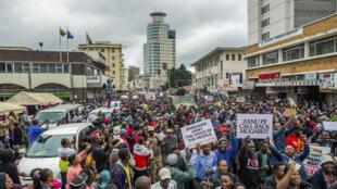 Une foule tient des pancartes et scande des slogans lors d'une manifestation demandant le départ du président du Zimbabwe Robert Mugabe, le samedi 18novembre à Harare.