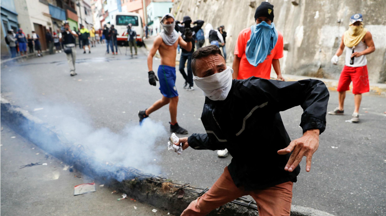 Un manifestante devuelve un recipiente de gas lacrimógeno mientras se enfrenta a la Guardia Nacional de Venezuela durante una protesta cerca de uno de sus puestos en Caracas, Venezuela, el 21 de enero de 2019.