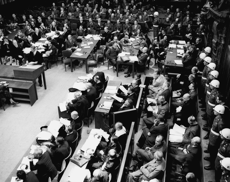 Sobre esta imagen de archivo del 20 de noviembre de 1945, la policía militar hace fila en esta primera audiencia en Núremberg. En primer plano, los acusados alemanes con su abogado colectivo sentado delante de ellos.