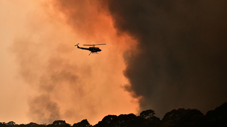 Un helicóptero sobrevuela un incendio forestal cerca de Bilpin, a 90 km al noroeste de Sídney, Australia, el 19 de diciembre de 2019.