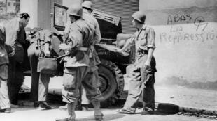 Des soldats français examinent un véhicule militaire au pare-brise cassé le 22 juillet 1956, pendant la guerre d'Algérie.