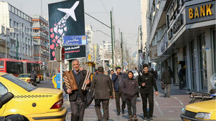Iranians walk past a poster honouring the victims of a Ukrainian passenger jet accidentally shot down in the capital last week, in front of the Amirkabir University in the capital Tehran, on January 13, 2020.