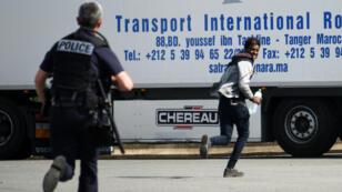 Un policier chasse un jeune migrant dans les environs de Calais, le 5 juillet 2017.