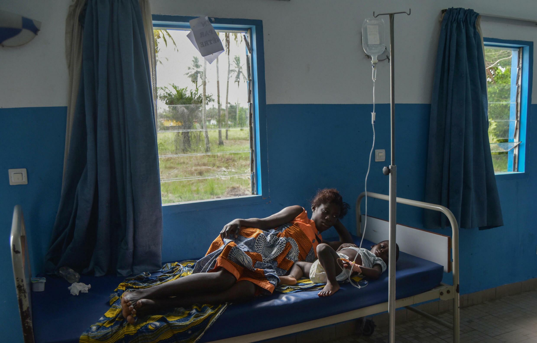 Une femme près d'un enfant ayant contracté le paludisme à Jacqueville, en Côte d'Ivoire, le 19 avril 2019