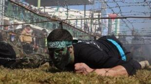 شبان من حماس يقدمون عرضا عسكريا بعد انتهاء مخيم تدريبي