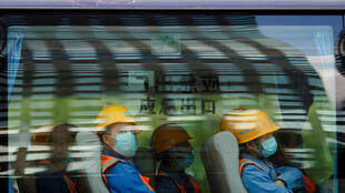 Workers leave a construction site at the end of their shift in the Central Business District in Beijing, China, April 16, 2020.