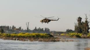 Un hélicoptère survole le Tigre, près de Mossoul, pour trouver d'éventuels survivants le 21 mars 2019