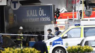 Les forces de police restreignent l'accès au camion qui a servi à l'attaque terroriste, à Stokholm, le 7 avril 2017.