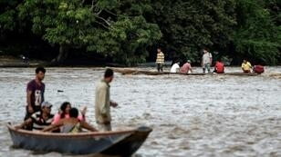Venezuelans take boats from one muddy shore to the other to buy supplies from Colombia or journey onwards