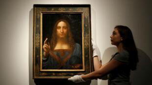 Empleada de la casa de subastas Christie's posa junto al Salvator Mundi de Da Vinci.