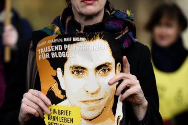 ناشطة من منظمة العفو تحمل صورة بدوي خلال احتجاج أمام السفارة السعودية في برلين