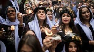 عراقيات إيزيديات يشاركن في احتفالات عيد رأس السنة أمام معبد لالش قرب دهوك (430 كلم شمال غرب بغداد) في 18 نيسان/أبريل 2017