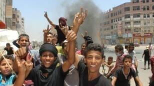 شبان يمنيون يلوحون بإشارة النصر خلال تظاهرهم احتجاجاً على غلاء الأسعار في عدن في 5 أيلول/سبتمبر 2018