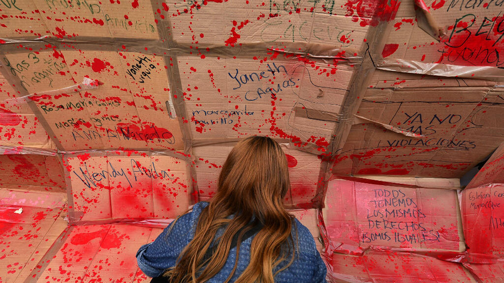 Una mujer escribe nombres de víctimas de violencia de género durante una manifestación contra los feminicidios en el Día Internacional de la Mujer. Tegucigalpa, Honduras, el 8 de marzo de 2019.