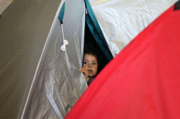 A migrant child peeps through the entrance to a tent in the main hall of the Ellinikon Airport, which has been closed since 2001.
