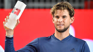 Austria's Dominic Thiem advanced to the second round of the US Open on Tuesday after opponent Jaume Munar retired following the second set