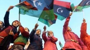 أطفال ليبيون يرفعون العلم الوطني إحياء لذكرى الثورة على معمر القذافي في 16 شباط/فبراير 2018 في العاصمة طرابلس