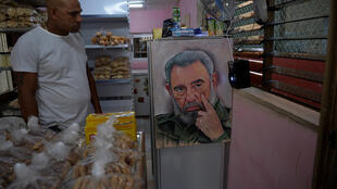 A man looks at a painting of late Cuban leader Fidel Castro at a bakery in Havana on January 26, 2021