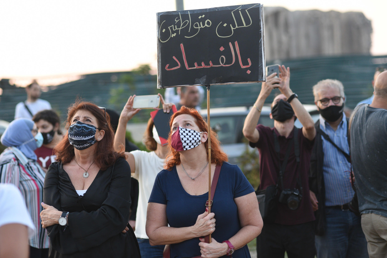 مشاركات ومشاركون في التجمع الذي نظم الأحد قرب مرفأ بيروت الذي دمره انفجار قاتل. المشاركون يشاهدون البالونات البلاستيكية ترتفع في السماء تكريما لضحايا الانفجار