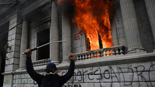A protester celebrates the burning of the Guatemalan Congress building, on November 21, 2020, in Guatemala City.