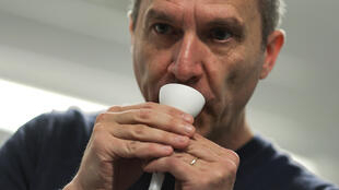 Professor Fabrice Bureau demonstrates how to use the saliva tests, which consist of a tube with a funnel for easy collection