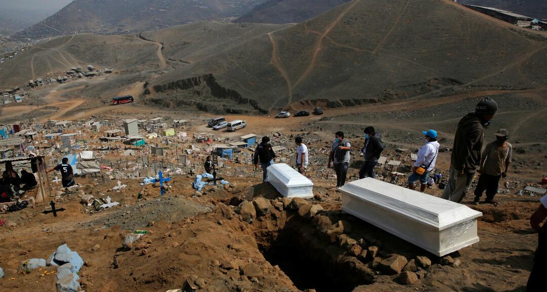 Dos familias a sus familiares, muertos a causa del coronavirus en el cementerio de Nueva Esperanza en Lima, Perú, el 27 de mayo de 2020.
