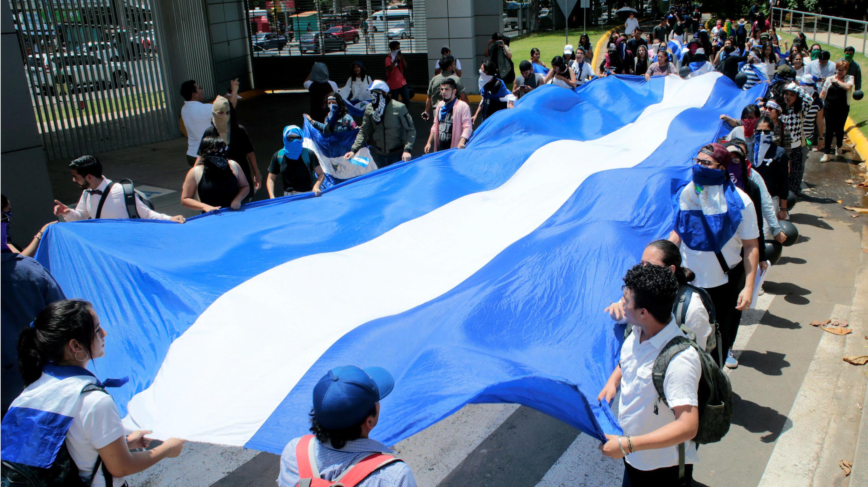 Archivo-Un grupo de manifestantes sostiene una gran bandera nacional durante una protesta contra el Gobierno del presidente Daniel Ortega en Managua, Nicaragua, el 18 de junio de 2019.