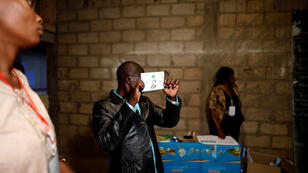Los trabajadores electorales participan del proceso de conteo de votos tras la celebración de las elecciones del 7 de octubre en Camerún.